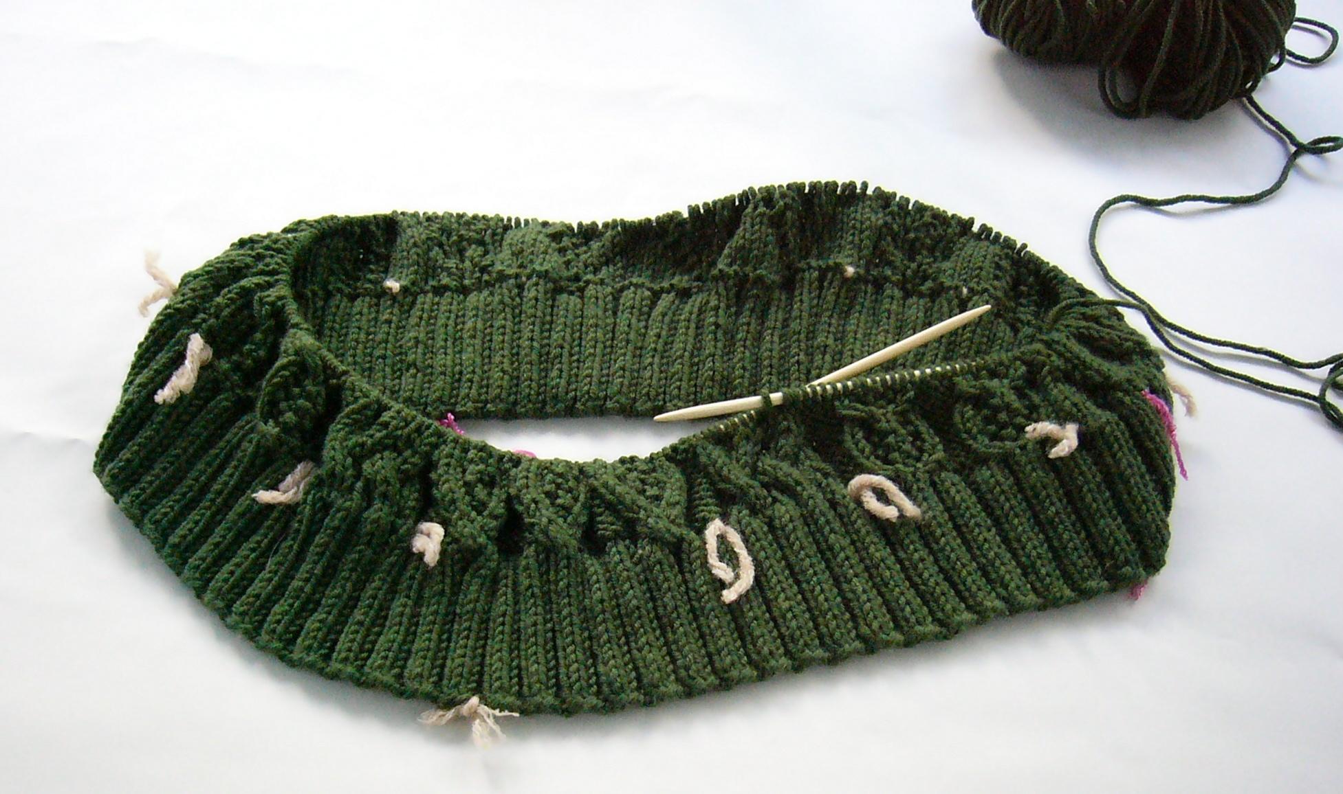 Rondbreien van een Aran-trui; de lichte draadjes scheiden de kabelpatronen