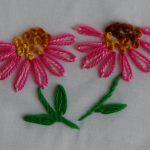 Bloemblaadjes uitgevoerd in madeliefjessteek in twee kleuren.