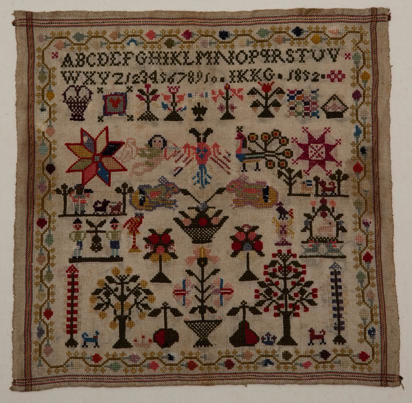 Merklap, kaasdoek met dunne wol geborduurd. Letters en cijfers. Jaartal 1852. Initialen: IKKG. Twee zelfkanten, twee kanten omzoomd. Geborduurd met veel motieven: bloemen, bomen, pauw, sterren, dragers met druiventros.