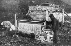 Een Tlingit-vrouw is een Chilkat-deken aan het weven, een man toont het patroonbord - Klukwan, Alaska, 1909.