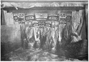 Een oude foto van een Chilkat in de maak. Let op de gewichten aan de losse kettingdraden.