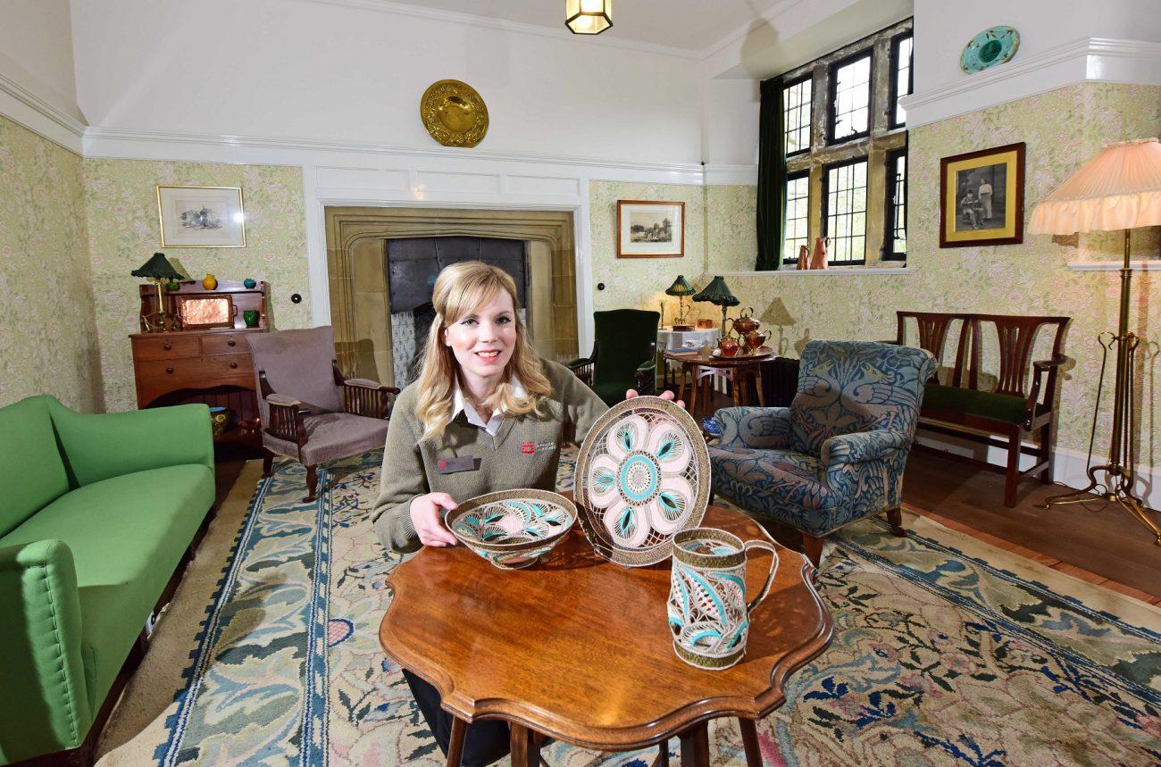 Victoria Conroy van English Heritage met werk van Pat Brunsdon in een in Arts and Crafts-stijl ingerichte kamer.