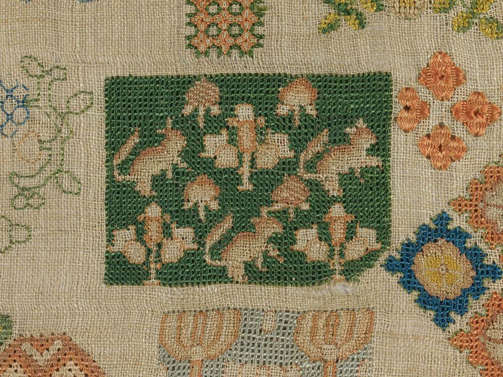 Detail van een 'spot motif sampler' uit de 17de eeuw. Linnen, geborduurd met veelkleurige zijde in verschillende steken, 21 x 52 cm.