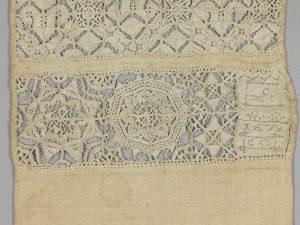 Detail van een pronkrol, in 1678 door Elizabeth Clowder gemaakt. Op deze pronkrol is zowel veelkleurig borduurwerk in zijde, witwerk en opengewerkt borduurwerk te vinden - 19 x 87 cm.