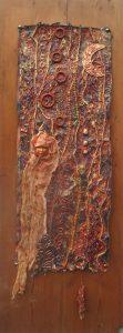 Crone - Crone is de naam die de Engelsen hebben voor een oudere wijze vrouw. In de godinnencultuur wordt een vrouwenleven in drie fasen ingedeeld: meisje-moeder-Crone. De achtergrond is fabric paper waarop kralen zijn geborduurd en de onderdelen bevestigd. Het hoofdje is van gips en voor de kraal en bloem zijn foam en Tyvek gebruikt.