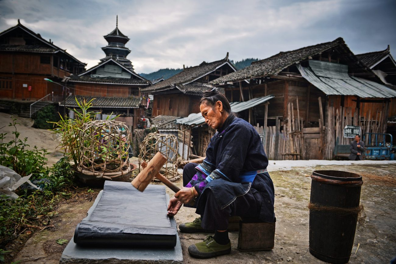 Een Dong-vrouw kalandert een doek, dat eerst met indigo is geverfd, Si Zhai, Liping Country - foto Wu Zeng Ou.