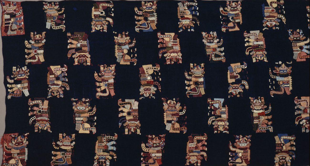 Mantel, vermoedelijk dodenmantel, van blauwe lamawollen stof met 53 met katoenen garen geborduurde motieven in telkens tien kleuren. Paracas-beschaving, circa 200 BCE - 100 CE, 240 x 88 cm.