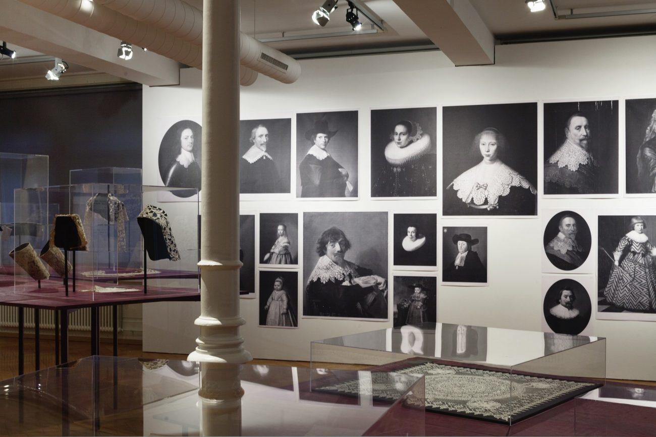 Overzichtsfoto van de tentoonstelling met afbeeldingen van kant op schilderijen - foto Susanne Stauss.