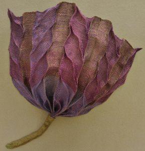 Ank Hazelhoff, Bloem. Deze bloem is geweven met koperdraad en diverse tinten glanskatoen en is na het weven in model gevouwen op lijnen die in het patroon van het weefsel zitten.