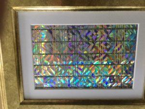 Marijke Jochijms, Glitters. Dit kleine ingelijste werkstuk is geweven in een variatie op de linnenbinding. Het gebruikte materiaal is katoen, blauw glitterdraad en stroken holografisch karton.