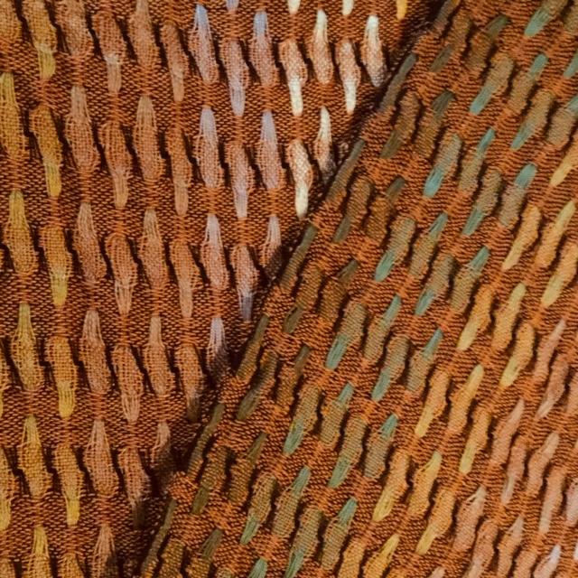 Marijke Jochijms, sjaal. Deze sjaal is geweven in de schijndubbeltechniek. Het gebruikte materiaal is gemerceriseerde katoen in verschillende tinten bruin, beige, groen en geel, geïnspireerd op de herfst en de kleuren van de boombladeren.