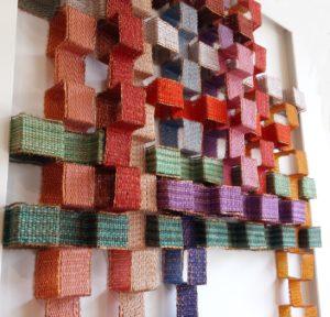 Marijke Scheepstra, Magisch vierkant. Het werkstuk is samengesteld door bandjes van 3 cm breed te weven. De weeftechniek is linnenbinding, uitgevoerd in verschillende kleuren borduurkatoen en koperdraad. Daarna heeft zij de bandjes gevouwen in blokformaat en het geheel samengevoegd tot een compositie in kleur met verschillende hoogtes.