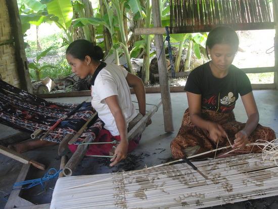 Weven in Wangaipu. Op de voorgrond het afbinden van de kettingdraden - Sumba ikat - Handwerkwereld